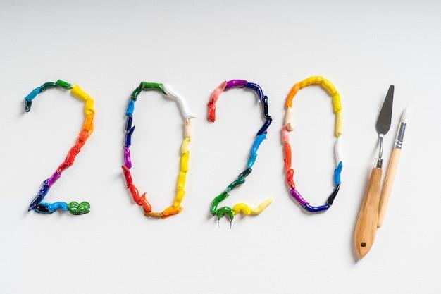 番号2020は、白いキャンバスに明るい油絵の具で描かれています。トップビューをクローズアップ。