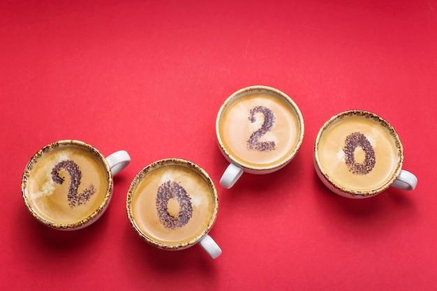 新しい2020年の始まりの概念は、コーヒーカップに描かれています。