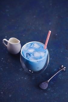 Матча синий чай со льдом в стакане на синем столе. цвет года 2020.