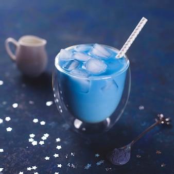 青いテーブルの上のグラスに氷と抹茶ブルーティー。 2020年の色。