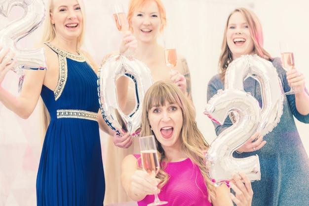 Женщины празднуют новый 2020 год с шампанским