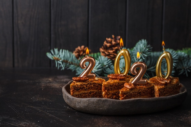 Новый год 2020. праздничный торт со свечами на темном столе, копией пространства.