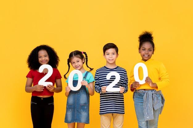 笑顔で2020の数字を保持しているかわいい混血の子供たち
