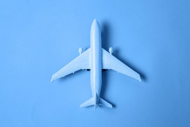 2020年の古典的な青の背景のトレンディな色のシンプルなフラットレイアウトデザインおもちゃの飛行機。明るいマクロ色。飛行機での旅の旅チケットツアー