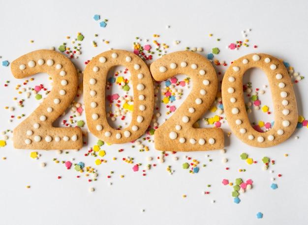 Разноцветная выпечка сахарного топинга и пряник в виде цифр 2020 на белом фоне