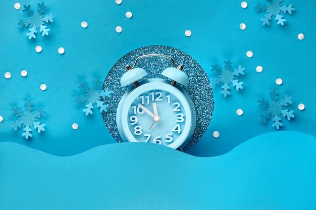 明けましておめでとう2020!紙の穴に目覚まし時計、青い色の紙の上にフラットレイアウト