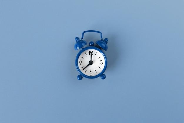 Малый будильник на пастельной предпосылке в классическом голубом цвете, конце-вверх, взгляд сверху. минимальный стиль ретро. тайм-менеджмент, цвет концепции 2020 года. скопируйте место для текста. горизонтальная ориентация