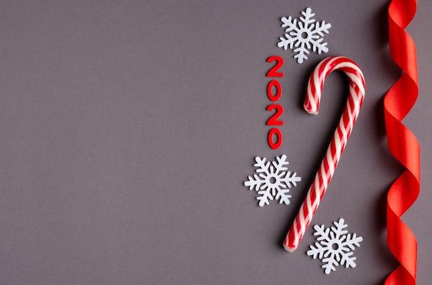 Красный леденец на палочке, номер 2020, композиция ленты и белые снежинки на темном фоне, новый год и рождественские праздники.