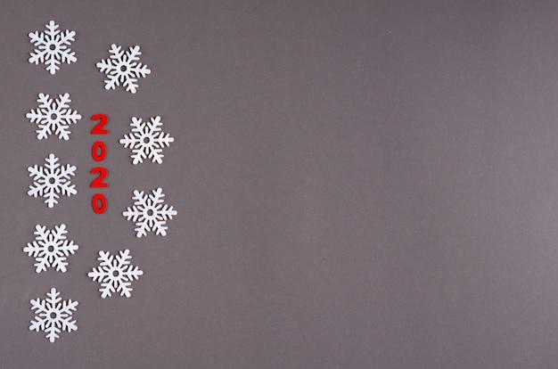 Красный номер 2020 и композиция белые снежинки на темном фоне, новый год и рождественские праздники.