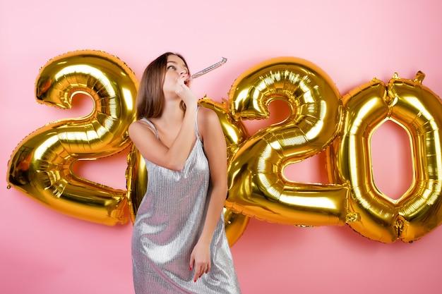 ピンクで分離された2020年風船でクリスマスパイプを吹いて新年を祝う女性