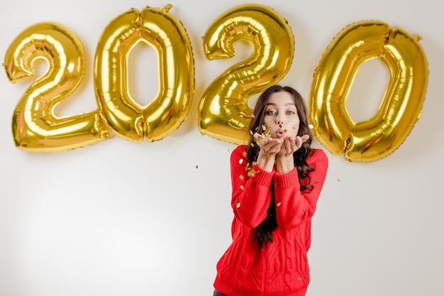 2020年の新年の風船の前に銀の紙吹雪を吹く赤いセーターの女性