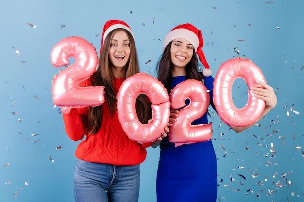 Две улыбающиеся женщины в шляпах санта-клауса с розовыми воздушными шарами нового года 2020, изолированных на синем
