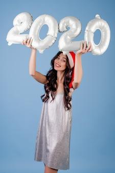 クリスマス帽子とドレスを着て2020年の風船を保持している女性