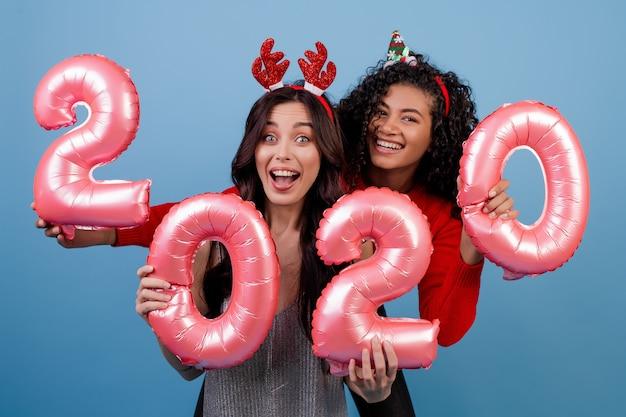 Счастливые многорасовые девушки с воздушными шарами 2020 новогодних и смешных обручей, изолированных на синем