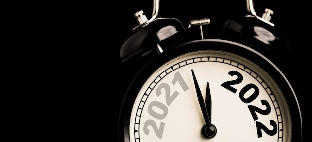 2021 and 2022 on black alarm clock  with copy space on black background and copy space , merry christmas and happy new year concept.