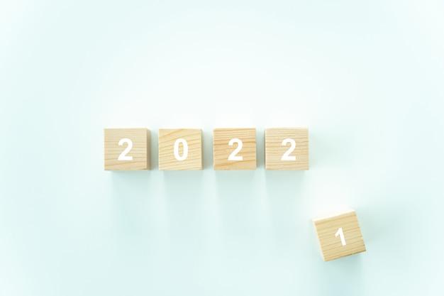 2021-2022年の白い背景の木製ブロックの言葉、2022年を祝う新年あけましておめでとうございますの概念と今年の2021年のさようなら。