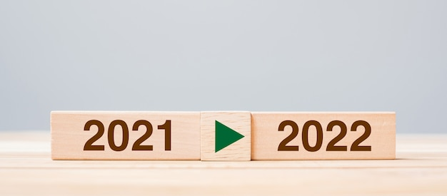 テーブルの背景に2021年と2022年の木製ブロック。解決策、戦略、カウントダウン、目標、変更、年末年始の概念
