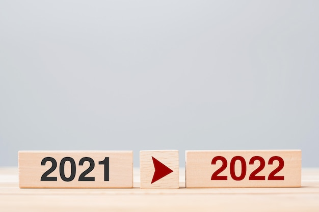 Деревянный блок 2021 и 2022 годов на фоне стола. решение, стратегия, обратный отсчет, цель, изменение и концепции новогодних праздников