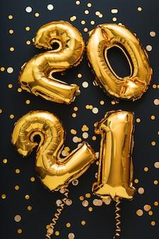 색종이, 축제 장식이있는 2021 풍선 골드 텍스트. 새해 복 많이 받으세요.