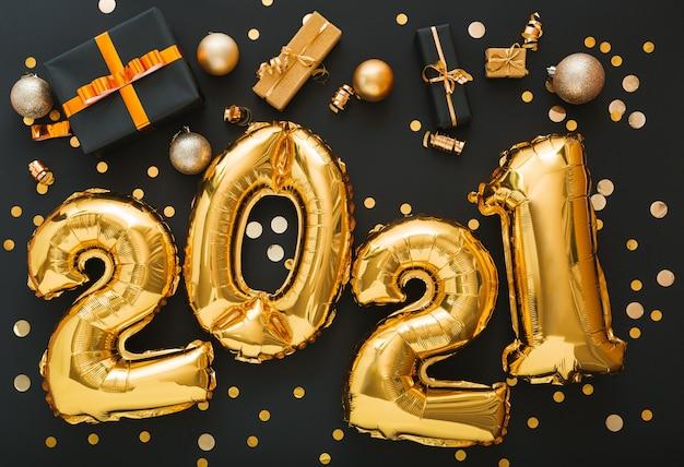 색종이, 선물 상자, 금 공, 축제 장식이있는 2021 풍선 골드. 새해