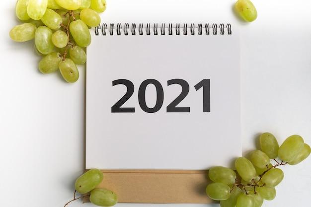 Календарь 2021 года в центре в окружении счастливого винограда