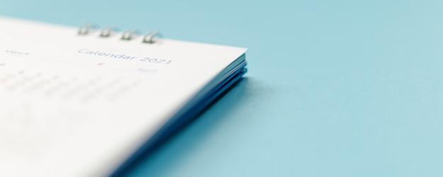 青い背景のビジネスプランニング予定会議の概念に関する2021年のカレンダーページ