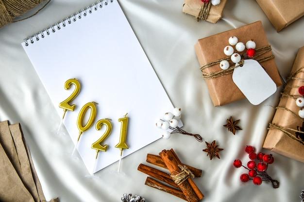 2021년 촛불 샴페인 색 실크 배경에 장식이 있는 선물과 함께 크리스마스 텍스트를 낭비하지 마십시오. 공간을 복사합니다. 공예 판지로 만든 태그가 있는 친환경 포장된 선물. 새해