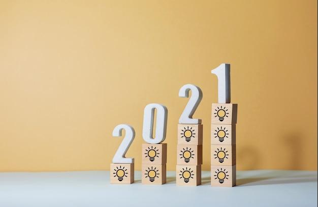 Идеи идей для творчества и вдохновения 2021 года с лампочкой и номером текста на деревянном блоге