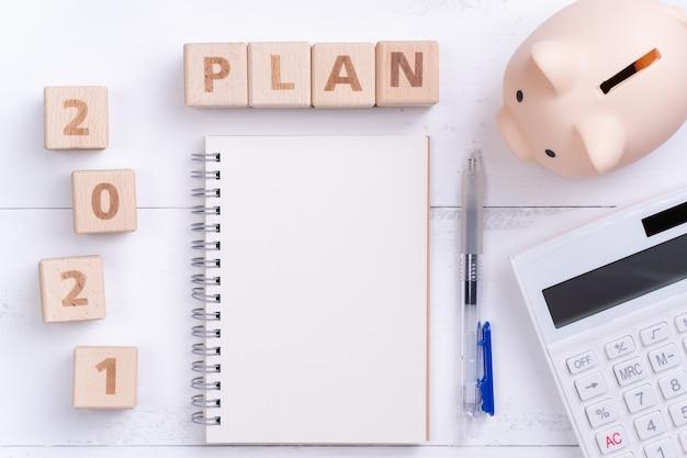 Концепция финансового плана 2021 года с пустой записной книжкой, копилкой, калькулятором и деревянным блоком.