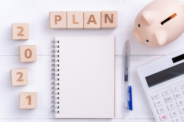 2021 financial plan concept with blank notebook, piggy bank, calculator and wooden block.