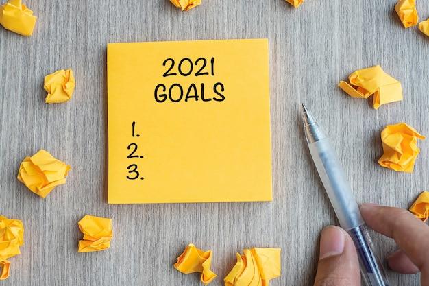 Цель 2021 года на желтой записке с бизнесменом, держащим ручку и крошащуюся бумагу