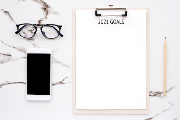 2021 goals on blank note paper with copy space for text and smartphone with blank screen on white marble