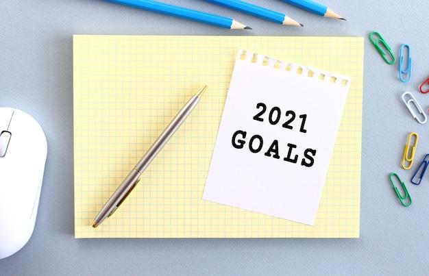 2021 년 목표는 사무용품 옆에 노트북 위에 놓인 종이에 적혀 있습니다. 비즈니스 개념.