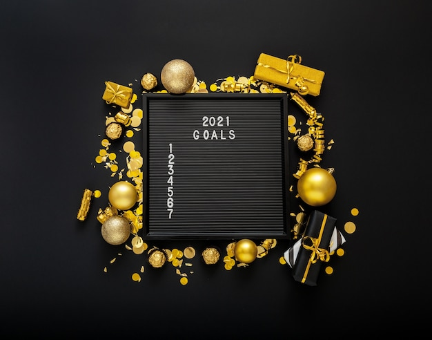 2021 goals list on black letter board in frame made of gold christmas festive decor.