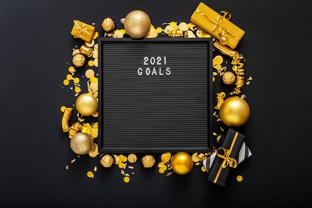 2021 목표는 검은 색 바탕에 골드 크리스마스 축제 장식으로 만든 프레임에 편지 보드를 나열합니다.