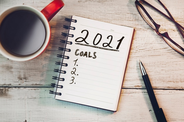 2021 goals on notepad and cup of coffee
