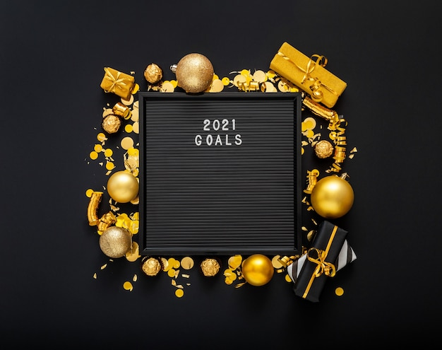 2021 goals text on black letter board in frame made of gold christmas festive decor.