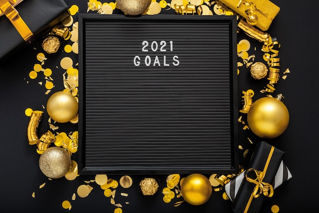 2021 goals text on letter board in frame made of gold christmas festive decor on black background.