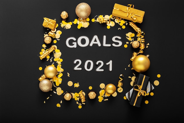 골드 크리스마스 축제 장식으로 만든 프레임의 검은 색 표면에 2021 목표 텍스트 글자
