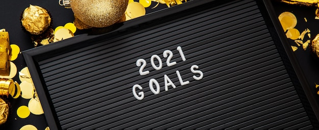 블랙 골드 크리스마스 축제 장식으로 만든 프레임의 문자 보드에 2021 목표 텍스트. 확대.