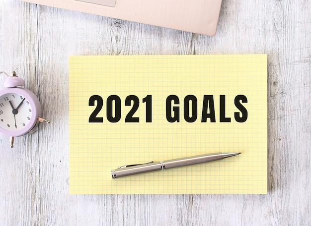 노트북 옆 나무 작업 테이블에 누워 노트북에 작성된 2021 목표 텍스트