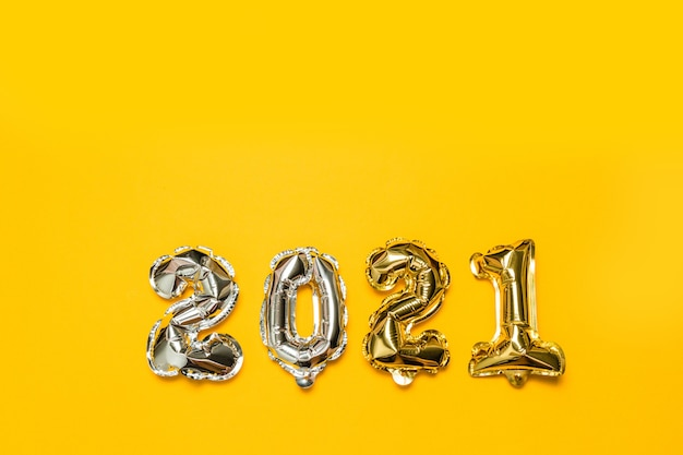 노란색 배경에 2021 금색과 은색 호일 풍선 번호. 새해와 크리스마스