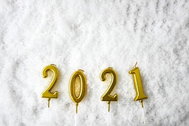 하얀 눈 배경에 2021 골드 촛불입니다. 텍스트를 위한 공간을 복사합니다. 즐거운 성탄절 보내시고 새해 복 많이 받으세요. 휴일 배경
