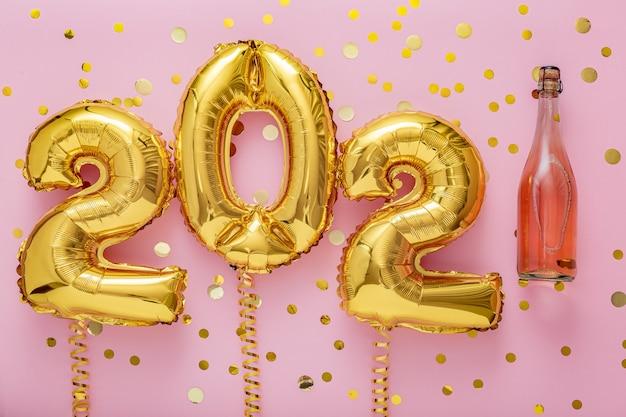 シャンパンボトルとグラスと2021年の黄金の風船。青い背景に新年あけましておめでとうございます。
