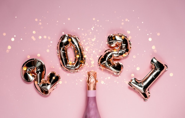 2021 golden foil balloons numbers with pink champagne and bokeh. top horizontal view copy space new year and holiday concept