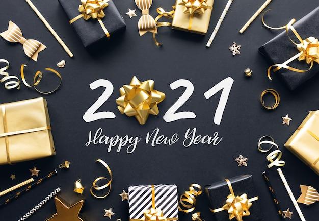 2021年明けましておめでとうございますお祝いのコンセプト暗い背景に金色のギフトボックスと飾り。冬の季節と記念日