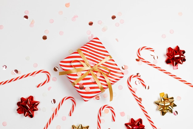 2021 happy new year frame composition. christmas striped design gifts boxes, golden and red bow, candy cane, glitter light on a white background with copy space. flat lay, top view