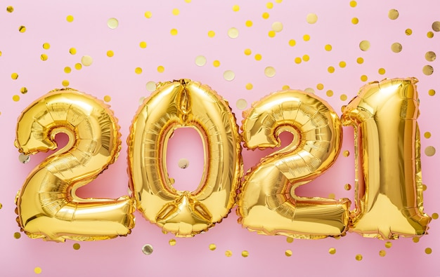 2021 happy new year gold air balloons on pink background with confetti.