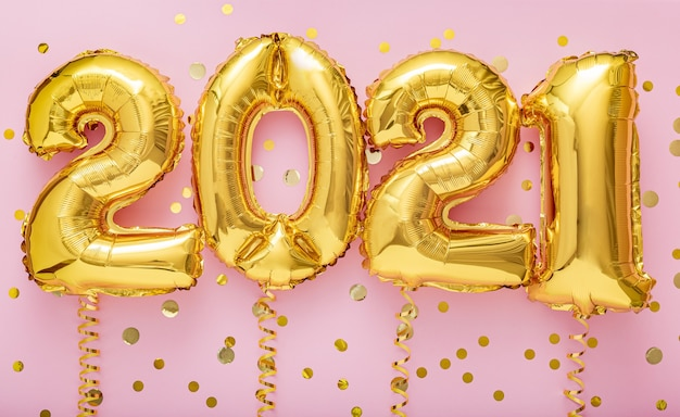 2021 happy new year gold air balloons on ribbons with confetti on pink wall.