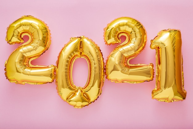 2021 happy new year golden balloons text at different heights on pink background. long web banner.